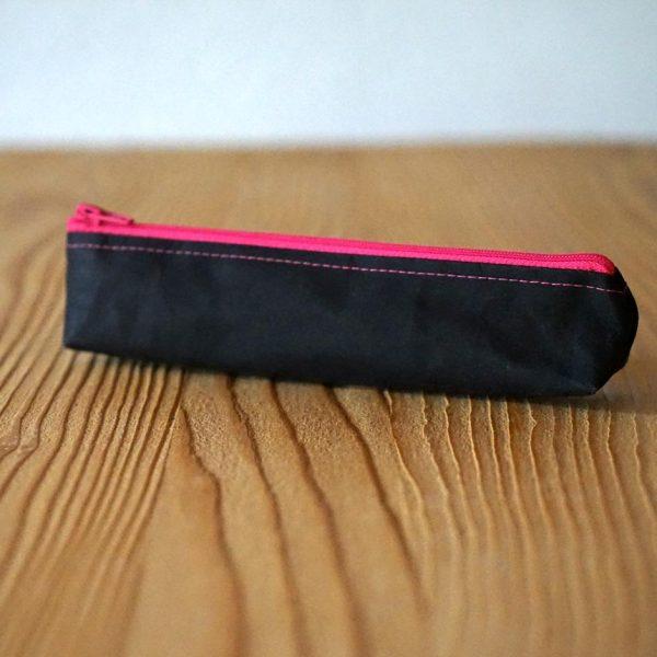 Handliches Stiftetui aus veganem Leder in Schwarz mit knalligem Reissverschluss in Pink.