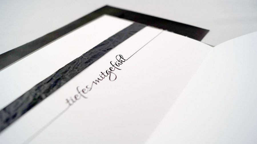 """Handgemachte Trauerkarte mit Stempeldruck einer Pusteblume auf Leinenstoff mit der Aufschrift """"Tiefes Mitgefühl"""""""
